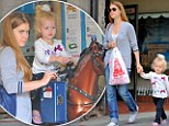 Giddy up! Amy Adams treats her daughter Aviana to an impromptu mechanical pony ride at the toy store