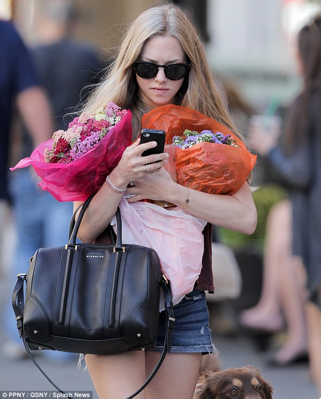 Multi-tasking: The star looked intensely at her phone while she clutched her bouquets and an iced coffee