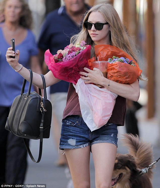 Snap happy: Amanda Seyfried took a photo of herself on her smartphone as she juggled her belongings on a stroll through downtown Manhattan on Wednesday