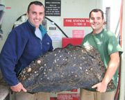 Scientists hold a large piece of asphalt collected from the volcano.