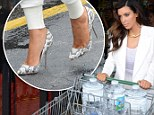 Kim Kardashian is not too posh to push as she wheels trolley around grocery store (tottering in killer heels)