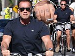 Bad to the bone! Arnold Schwarzenegger shows off tough guy tattoos... as he rides his bicycle