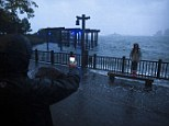Maya Vaknin, 12, of Manhattan, poses for a picture with her father in front of the rising tides near Battery Park