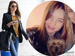 Weathering the storm with a smile: Miranda Kerr arrives at JFK then waits out Sandy with her pup