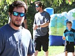 Safe and sound: Mark Wahlberg takes his son Michael to the park...while his brother Donnie's suffers Hurricane Sandy's aftermath