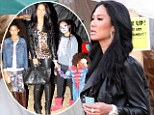 A bit overdressed! Kimora Lee Simmons teeters around a pumpkin patch in leather and leopard print with her children