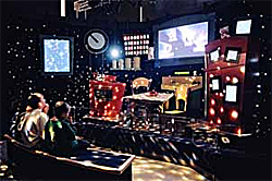 Image shows visitors in the Cosmic Kitchen Theater.  They are seated in a dark room in the lower left, and are viewing a stage set as a whimsical kitchen.  Lights flash over the kitchen like stars, while in the back a view screen highlights portions of what the narrator describes.