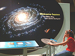 Image shows a student visiting an exhibit component.  The student at the lower right is touching a physical model of the galaxy and listening to an audio description, while looking at the large black mural of our swirling Milky Way Galaxy in the upper left.  A light blue panel with pictures and buttons is in the lower left.