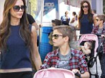 Bit of a role reversal! Romeo Beckham pushes baby Harper's stroller as Victoria guzzles blue Slushy on shopping trip