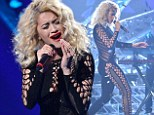 Hole-y moly! Rita Ora barely contains her modesty as she takes to The X Factor stage in a black crocheted catsuit