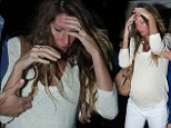 Someone looks ready for bed: Pregnant Gisele Bundchen shields her face following a night out to dinner
