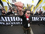 On the march: A man at the head of a group of Russian nationalists pictured here as he gestures in front of others carrying a large banner during a protest demanding the Kremlin take a harsher stance on migrants in Russia