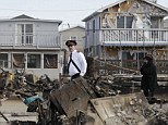 Shocked: A representative of the Salvation Army walks past homes destroyed by Superstorm Sandy in Breezy Point, Queens, New York