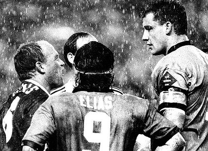 The power and the passion ... Wally Lewis and Mark Geyer go head to head during the 1991 series as Blues hooker Benny Elias looks on.