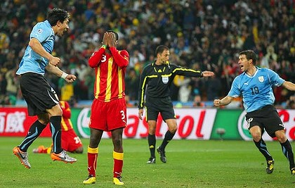 Uruguay players start celebrating while Asamoah Gyan, of Ghana, shows his devastation at missing a late penalty kick in extra time of the quarter-final at the Soccer City stadium.