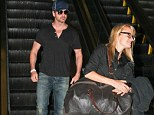 Travelling light: Gerard Butler let his female PA do the heavy lifting as she carried the actor's bag as he headed out from LAX to Dubai