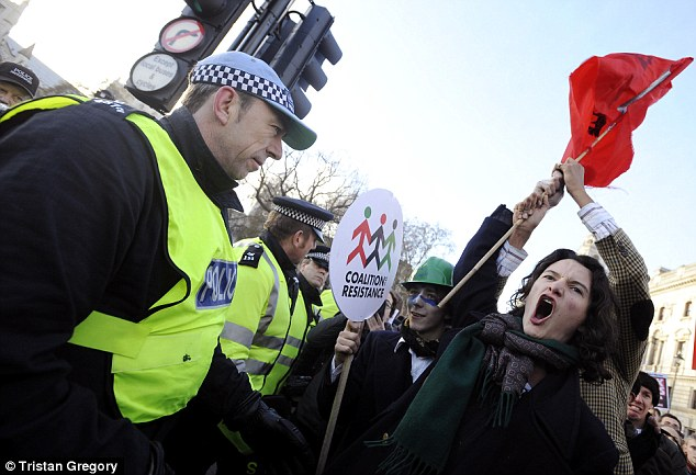 Defiant: Gilmour angrily brandishes a flag as police officers try to maintain order during the afternoon demonstration in Westminster