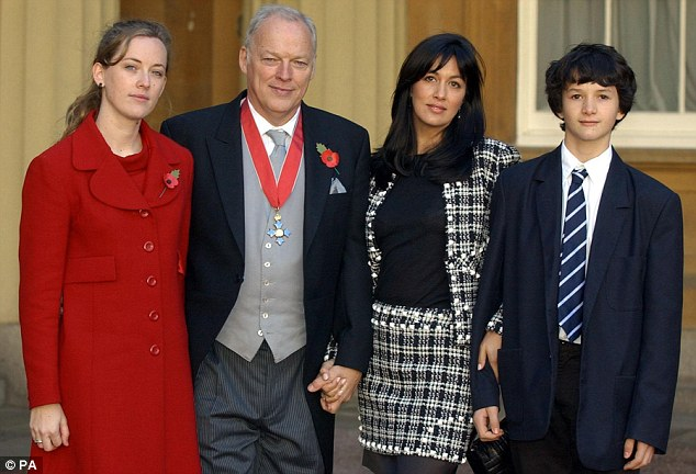 Best behaviour: Charlie with his parents as the guitarist received the CBE at Buckingham Palace in 2003