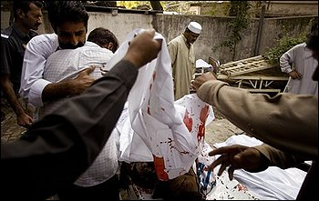 People look at dead bodies of a bombing victims at a local hospital in Rawalpindi, Pakistan on Monday, Nov. 2, 2009. An explosion occurred outside a bank near Pakistan's capital Monday, the latest in a wave of attacks by militants since the army launched a new military offensive against them last month. (AP Photo/B.K.Bangash)