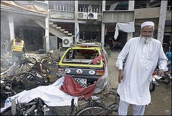 A Pakistani rescue worker stands at the site of bomb explosion outside a bank in Rawalpindi, Pakistan, Monday, Nov. 2, 2009. An explosion occurred near Pakistan's capital Monday, the latest in a wave of attacks by militants since the army launched a new offensive against them last month. (AP Photo/Anjum Naveed)