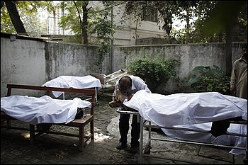 A man mourns over the body of his brother, a victim of a bombing, at a local hospital in Rawalpind, Pakistan, Monday, Nov. 2, 2009. An explosion occurred outside a bank near Pakistan's capital Monday, the latest in a wave of attacks by militants since the army launched a new military offensive against them last month. (AP Photo/Alexandre Meneghini)