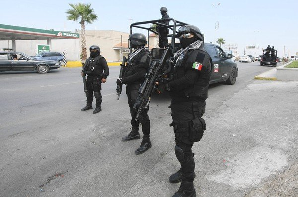 Coahuila state police guard a checkpoint in the city of Piedras Negras in September after a prison break staged by the Zetas cartel in the northern Mexican state.
