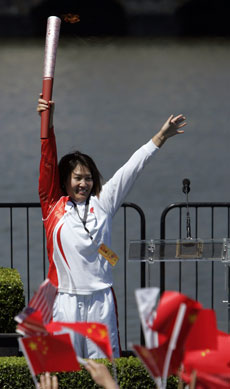 Chinese swimmer Lin Li waves the Olympic torch on Wednesday during the torch relay in San Francisco.