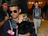 Something you want to tell us? Louis Tomlinson cuddles up to a baby as One Direction lands in London