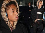 Little trendster: Jayden Smith arrives at airport in oversize head phones and funky fur-lined hoodie from own collection
