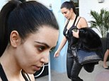 Ready for bed: Exhausted Kim Kardashian keeps her had down in her arrival back in Miami on Monday; for once she went without make-up