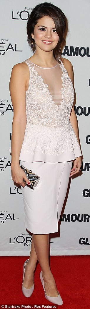 Stunning in snow white: The 20-year-old was dressed to kill in a plunging snow white lace peplum dress for the stylish event