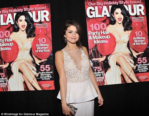Proud: Selena posed in front of huge banners of her recent cover of Glamour magazine, which is currently celebrating their 10 Amazing Women of the Year