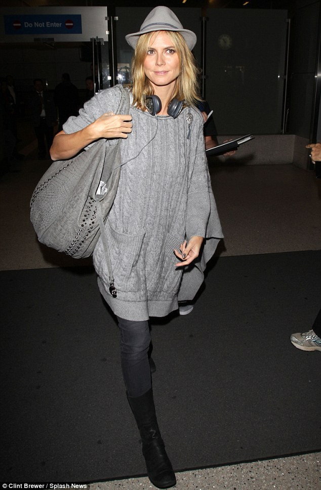 No fuss but still stunning: The make-up free 39-year-old wore an oversized grey knitted poncho, a pair of grey skinny leg jeans and black flat boots as she touched down at LAX airport