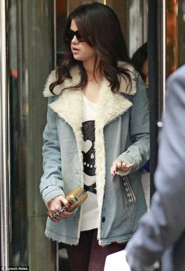 Armed and dangerous: Selena Gomez shows off her knuckle duster bag as she leaves her New York hotel