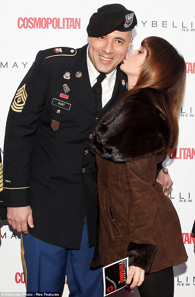 Charmed: Rose McGowan plants a kiss on NY Army Nat'l Guard Sgt. 1st Class Yueha at the Cosmpolitan Kisses for the Troops event