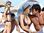 At least her hair is covered! Beach fanatic Rita Rusic dons Trilby and smooches toy boy lover as she debuts yet another miniscule bikini