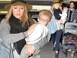 Family getaway: A happy Hilary Duff jetted out of LAX with her baby and husband Mike Comrie on Thursday