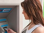 A young woman withdrawing money from a cash machine