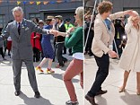 Prince Charles, Prince of Wales dances with Lisa Shannon at the Dance-O-Mat during a visit to Christchurch