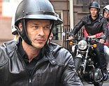 Paul Sculfor riding a motorcycle while filming with a blonde model in Downtown Manhattan