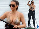 On the prowl! Kim Kardashian parades her generous curves in form-fitting wetsuit and leopard print bikini top