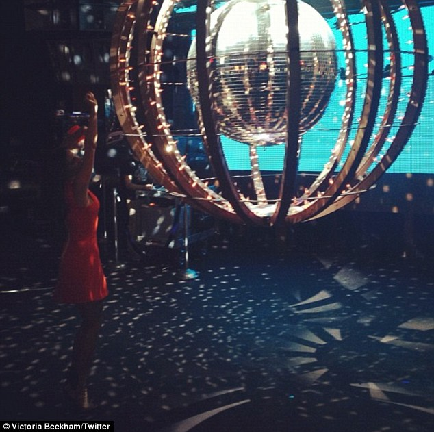 Dancing on her own: Victoria Beckham cuts a rug in an empty club featuring a very large disco ball, but it's just the setting for her latest photo shoot