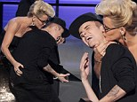 'I feel violated right now': Justin Bieber gets nuzzled on stage by maneater Jenny McCarthy as he wins three gongs at AMAs (but ex Selena Gomez fails to show up)