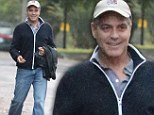 Dress down day: Gorgeous George Clooney tries to hide his movie star looks under a snap-back cap