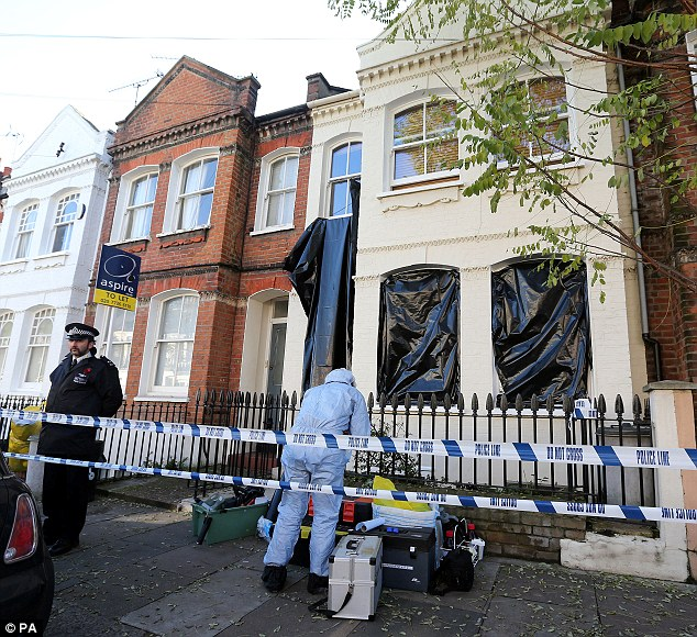 Hunt for clues: A forensic officer prepares to scour the scene in Fulham, where the body of Joseph Griffith was found yesterday morning. He had been stabbed seven times
