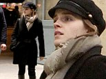 Oh là là! Emma Watson looks chic in a baker boy cap and boots as she arrives in Paris