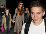 Heading for a Hollywood smile: Brooklyn Beckham shows off braces as Victoria takes the brood to London... leaving David behind in LA
