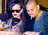 I'll drink to that: Rihanna topped up her glass while Chris puffed on a cigarette