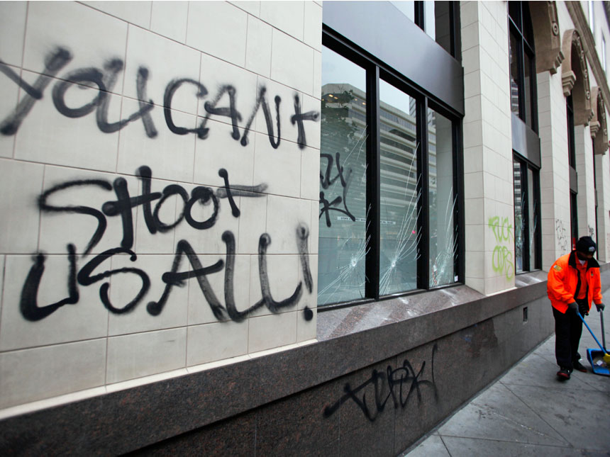 A worker sweeps the sidewalk near graffiti painted by protesters in downtown Oakland.