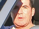 Larger than life: A fuller-faced Simon Cowell was photographed while taking a friend for a spin past his three Beverly Hills homes in his Ferrari 458 Italia Spyder